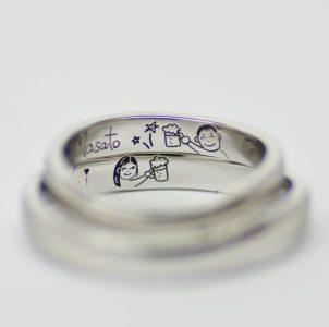 ふたりの似顔絵と乾杯シーンを手描き彫刻した結婚指輪